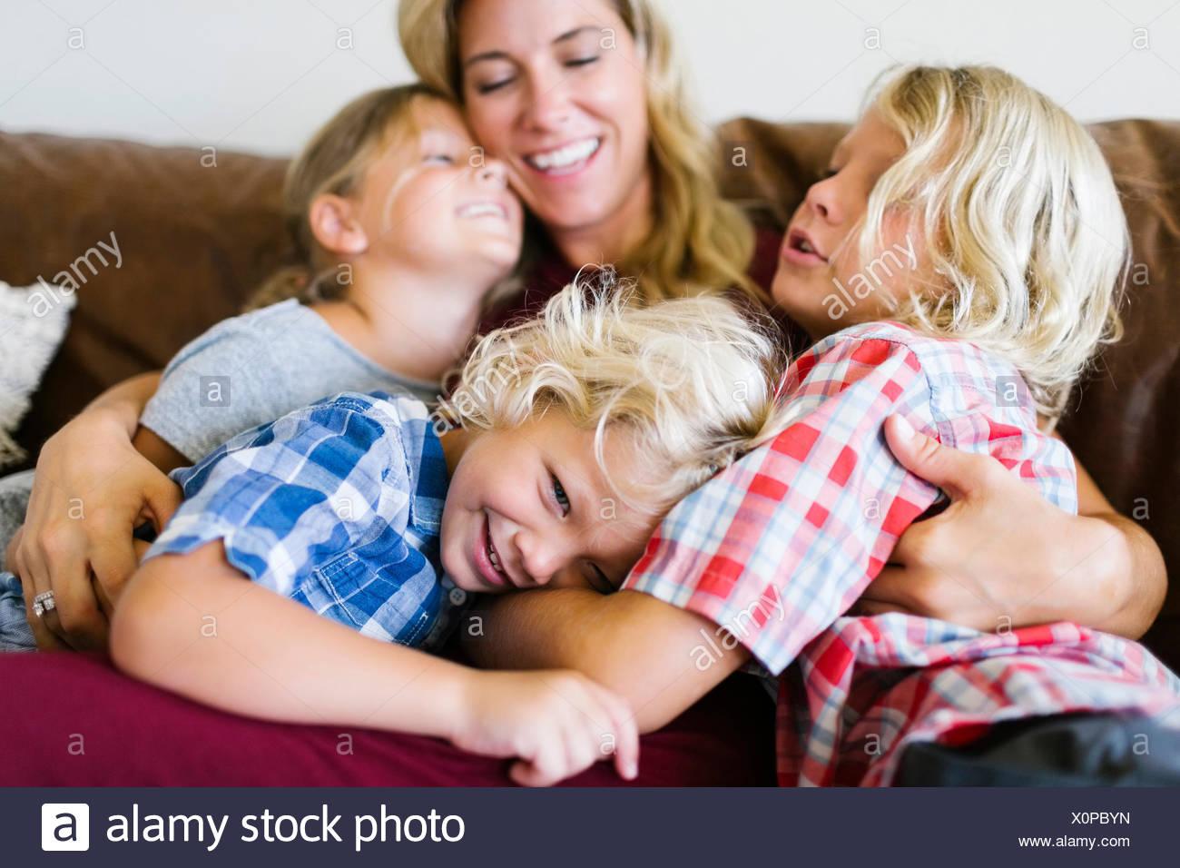 Madre e bambini (4-5, 6-7, 8-9) abbracciando in salotto Immagini Stock