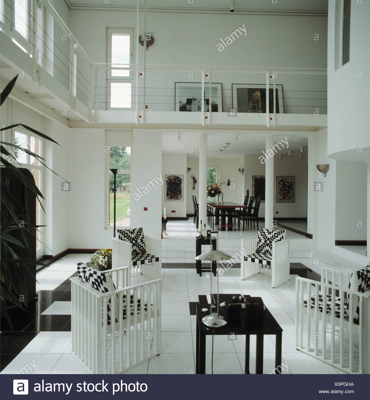 Bianco e nero cuscini su sedie bianche in doppia altezza openplan ...