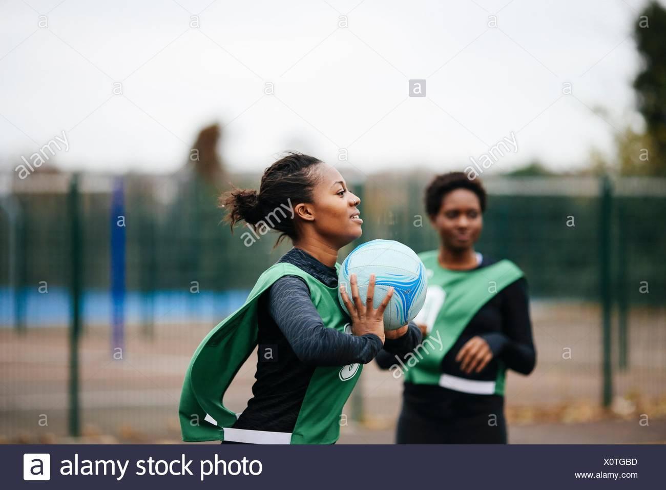 Giovane femmina adulta netball player a giocare su netball corte Immagini Stock