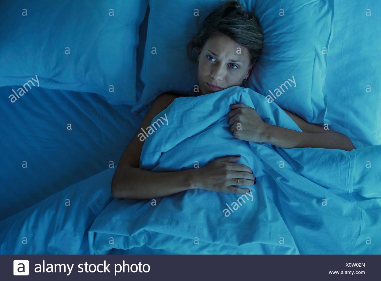La donna che giace da sola nel letto con espressione