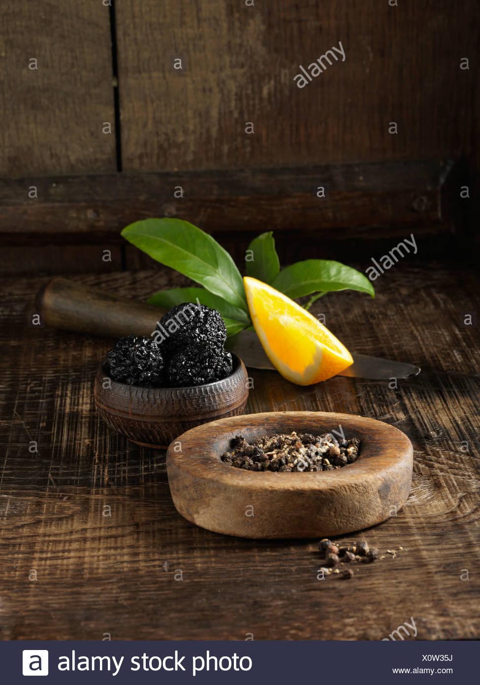 Tartufo nero, chicchi di pepe nero e arancione Foto Stock