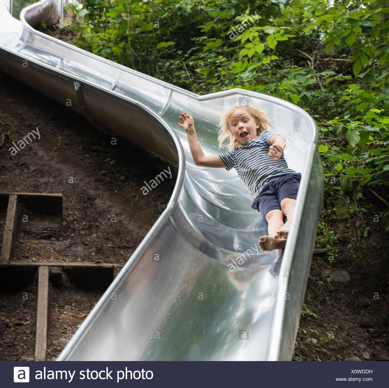 Ragazzo lo scorrimento verso il basso il parco giochi slitta Immagini Stock