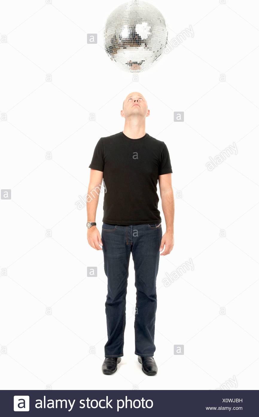 Uomo che guarda verso l'alto alla discoteca sfera dello specchio Immagini Stock