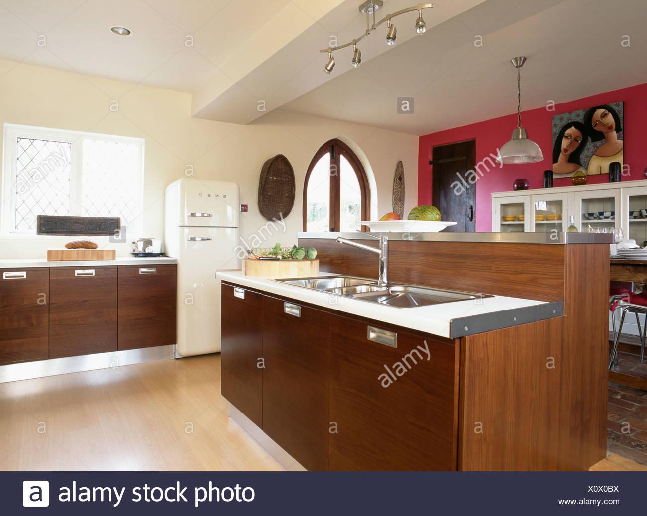 Parete rosa in grande e moderna cucina color crema con mobili di ...