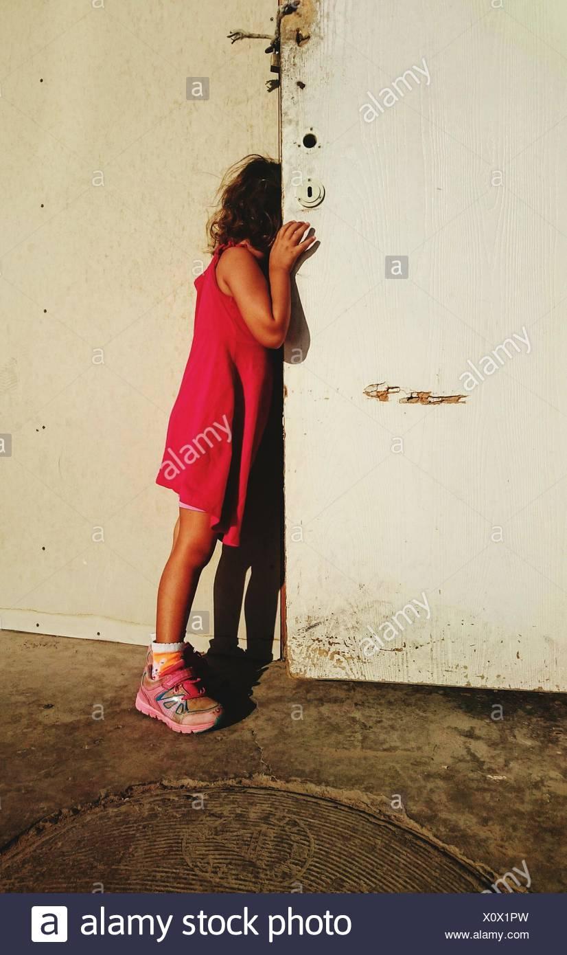 Vista laterale della ragazza spiata da porta Immagini Stock