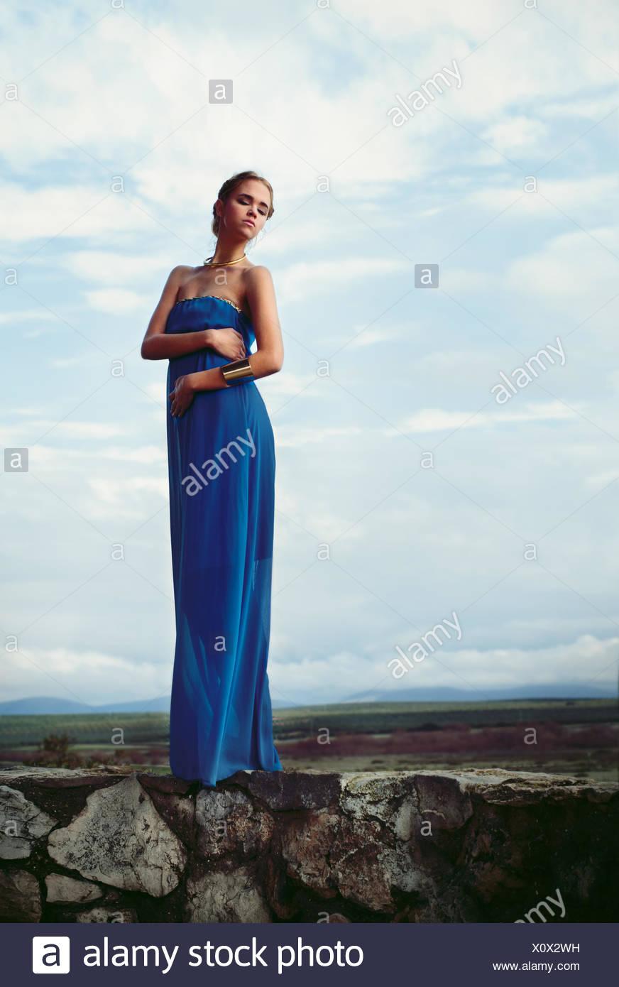 Donna che indossa blu abito lungo in piedi sul muro di pietra Immagini Stock