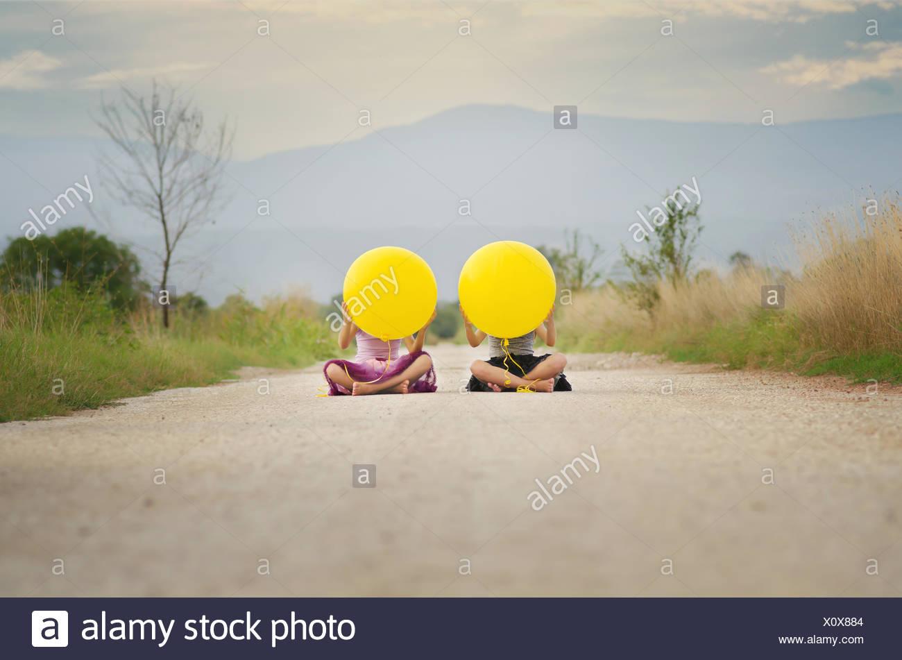 Due ragazze (6-7, 8-9) con palloncini Immagini Stock