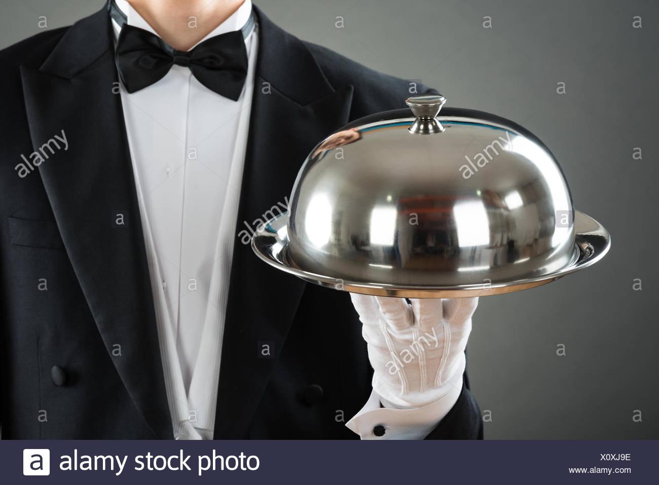 Sezione mediana del cameriere tenendo il vassoio con Cloche Immagini Stock