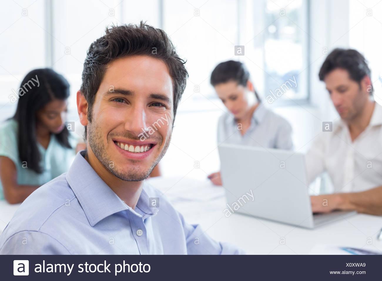 Imprenditore attraente sorridente sul posto di lavoro Immagini Stock