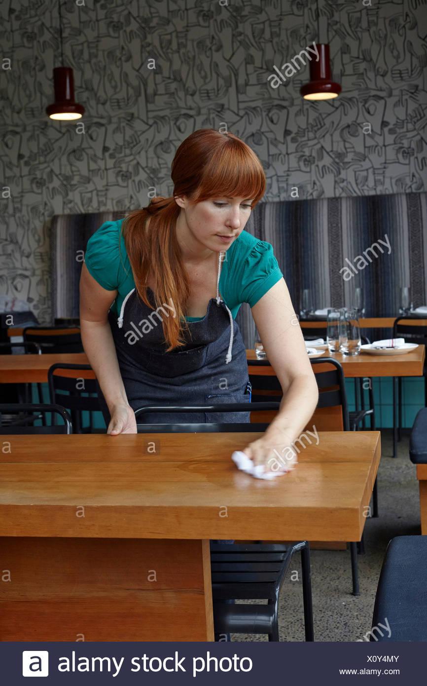 Metà donna adulta tabella di pulizia nel ristorante Immagini Stock