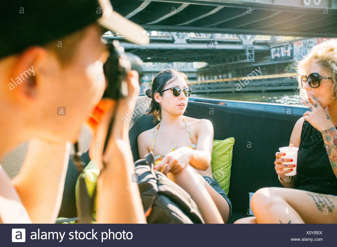 Uomo di fotografare le donne mentre poggia su barca Immagini Stock