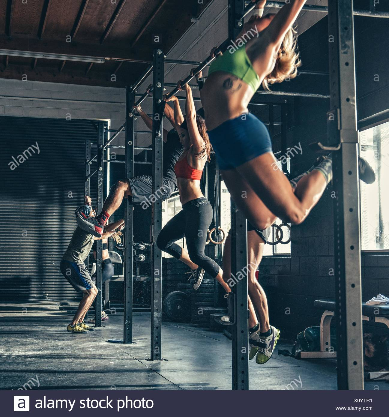 Fila di persone in formazione sulla barra di esercizio in palestra Immagini Stock