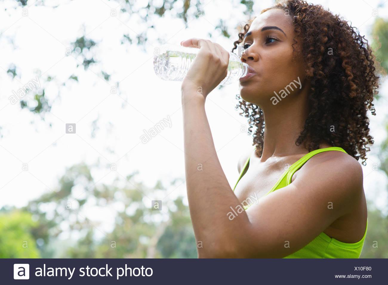 Metà donna adulta bere da una bottiglia d'acqua Immagini Stock