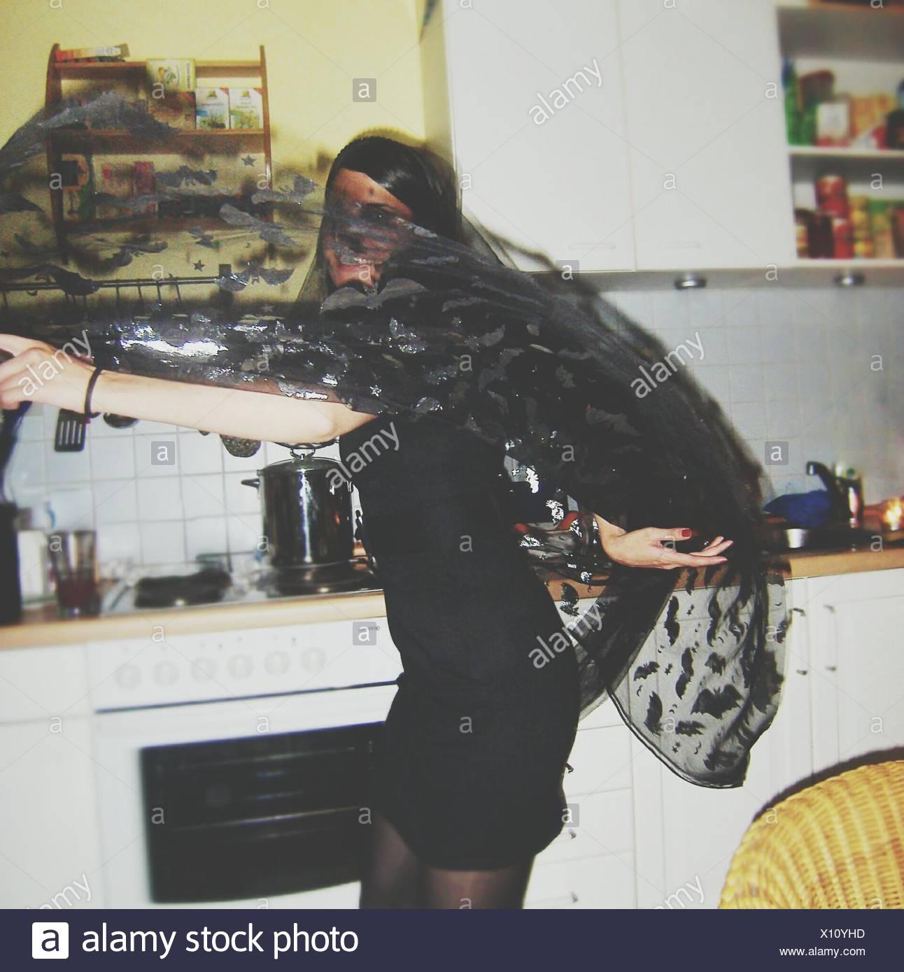 Giovane donna giocando con sciarpa a casa In Halloween Immagini Stock