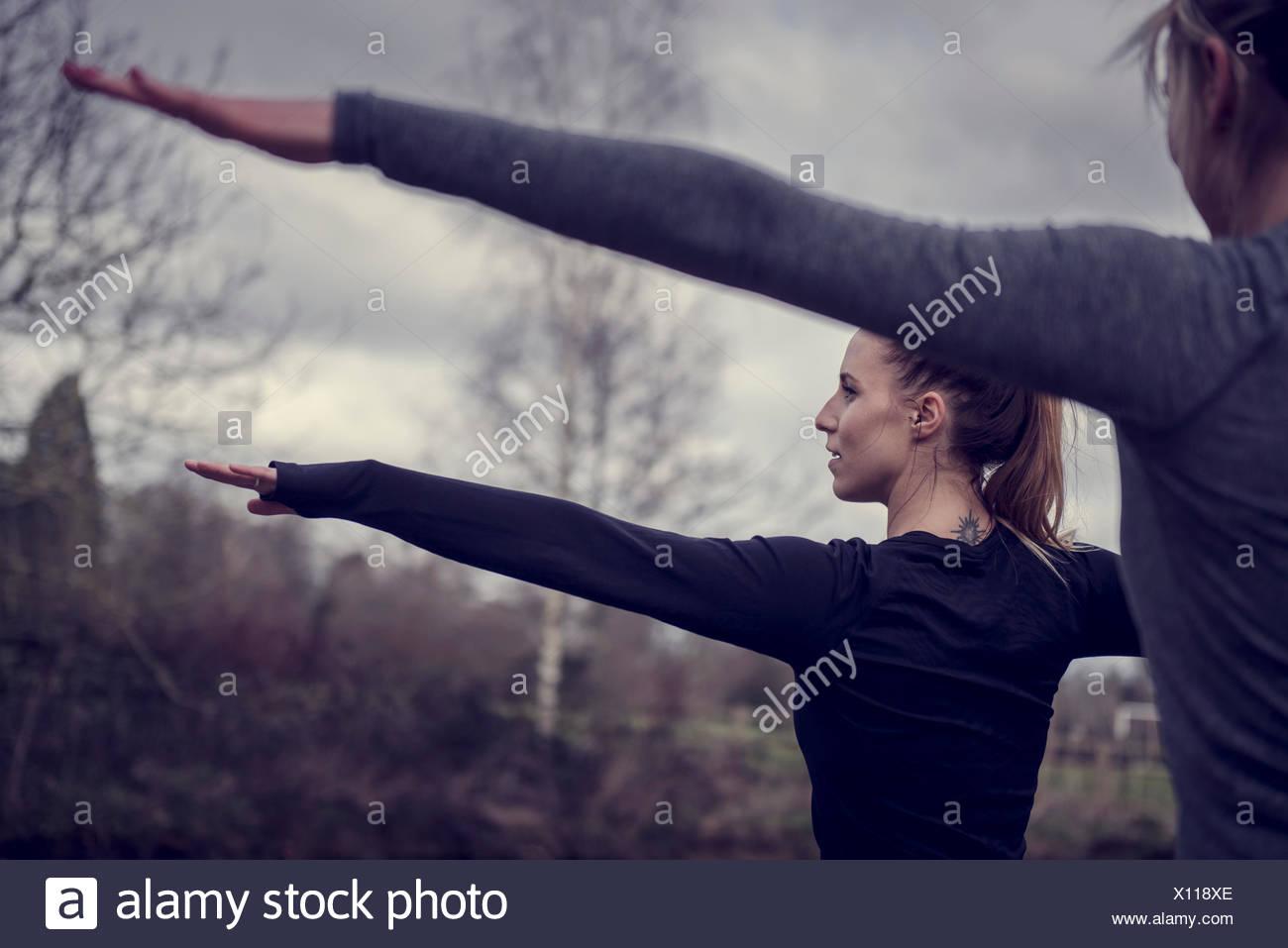Tagliate vista posteriore delle donne i bracci aperti stretching, guardando lontano Immagini Stock
