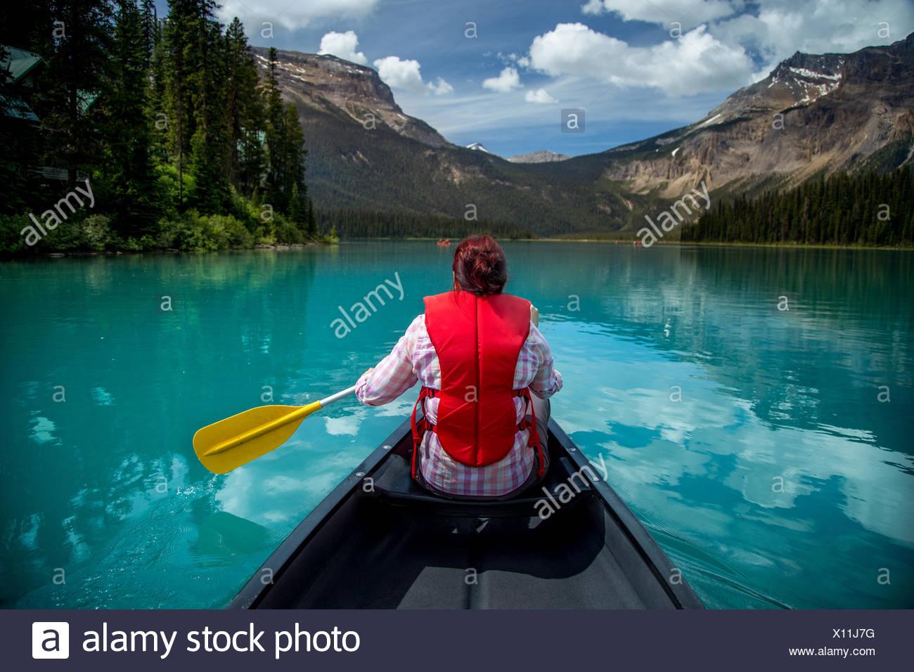 Donna in Canoa Lago Smeraldo, Parco Nazionale di Yoho, della Columbia britannica in Canada Immagini Stock