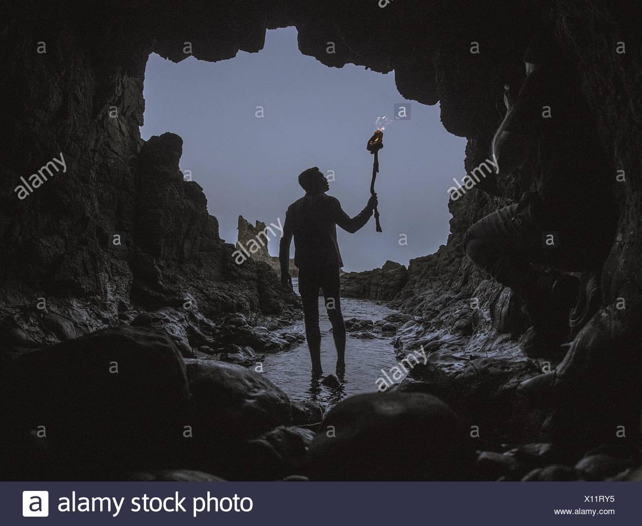 Uomo con torcia ardente a piedi nella grotta Immagini Stock