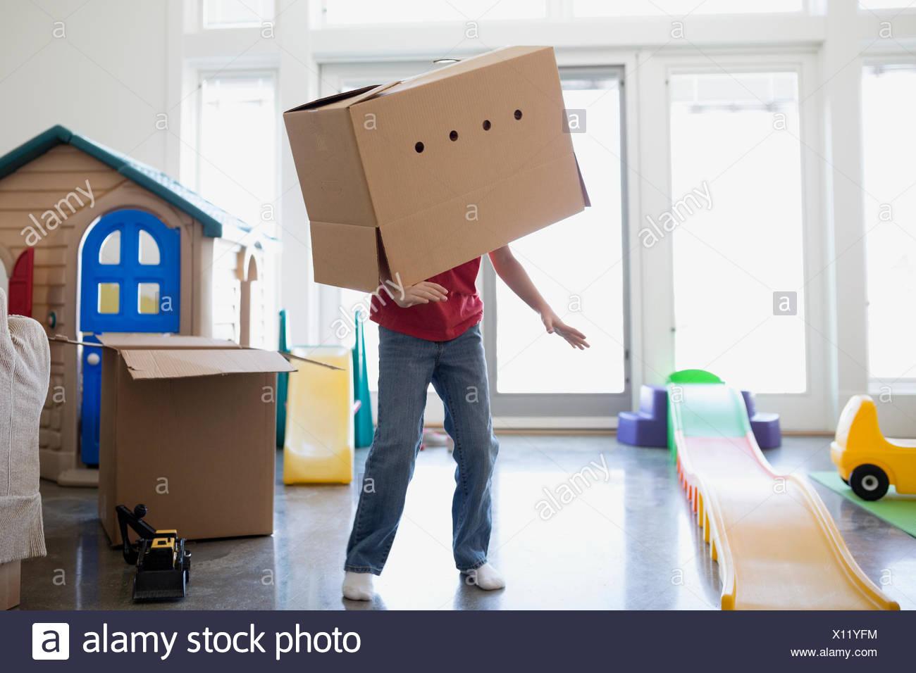 Giocoso ragazzo ballando con scatola di cartone sulla testa Immagini Stock