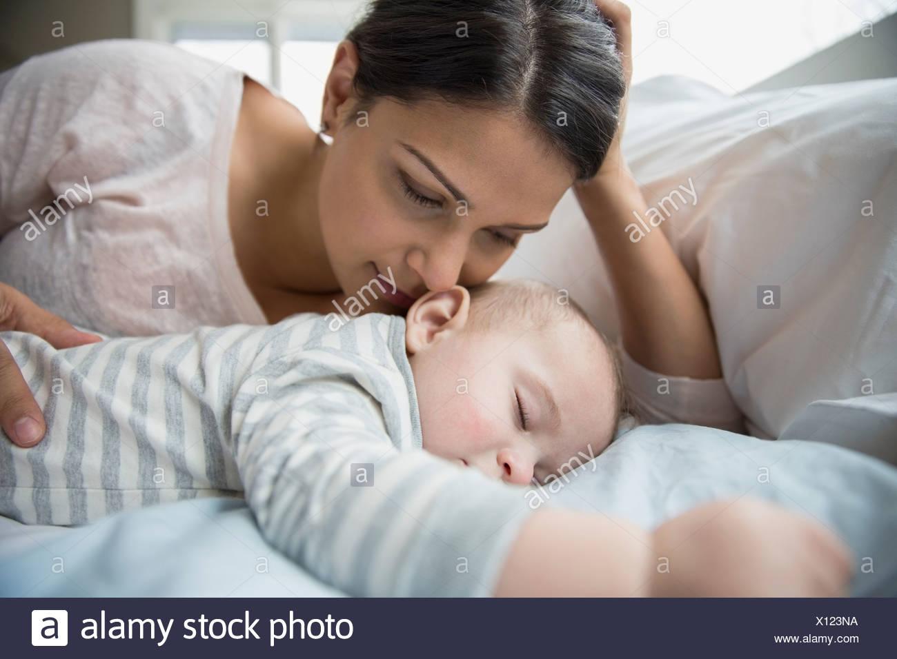 La madre guarda il bambino dorme sul letto Foto Stock