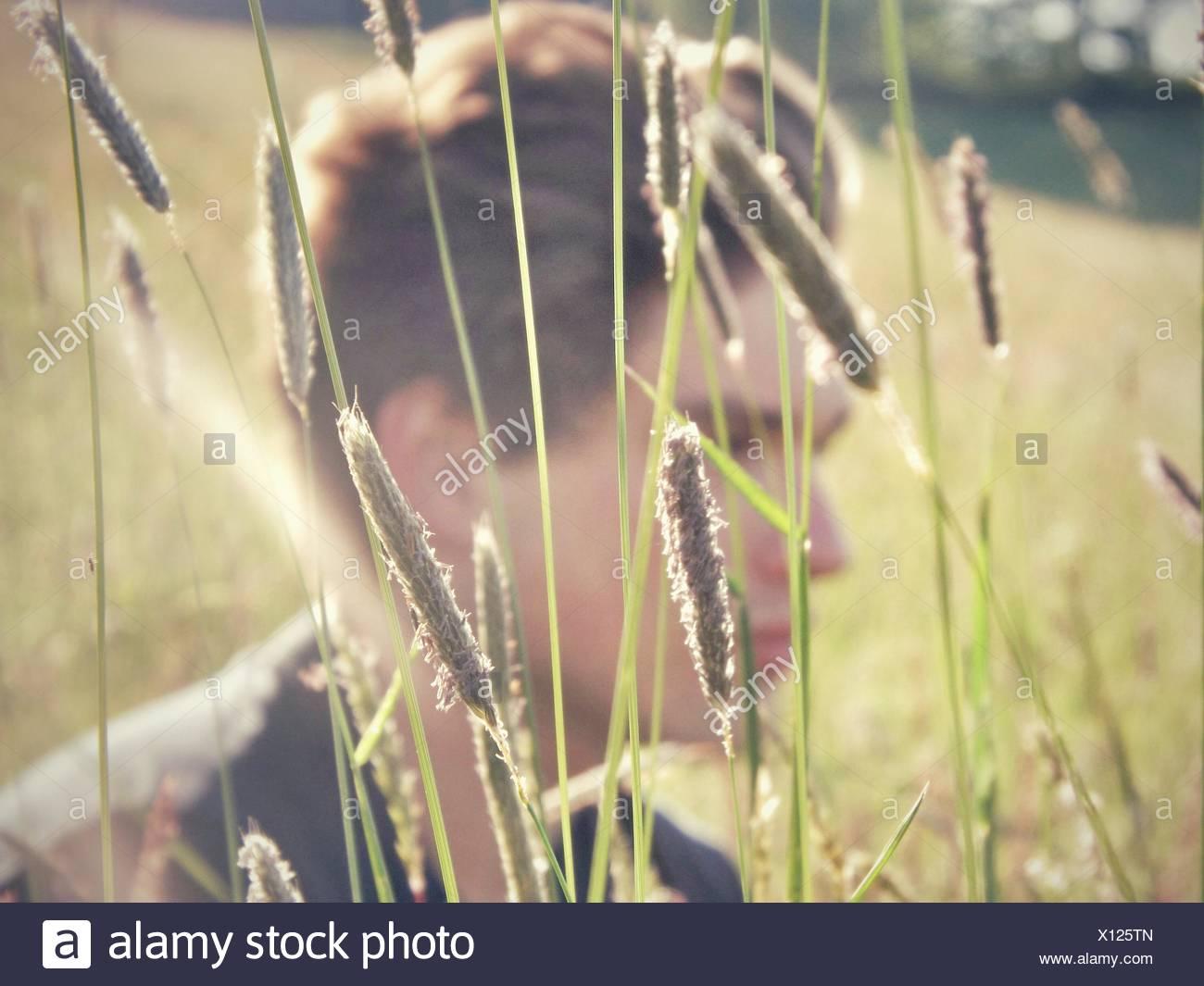 Close-Up vista laterale di un giovane uomo che guarda lontano con piante in primo piano Immagini Stock