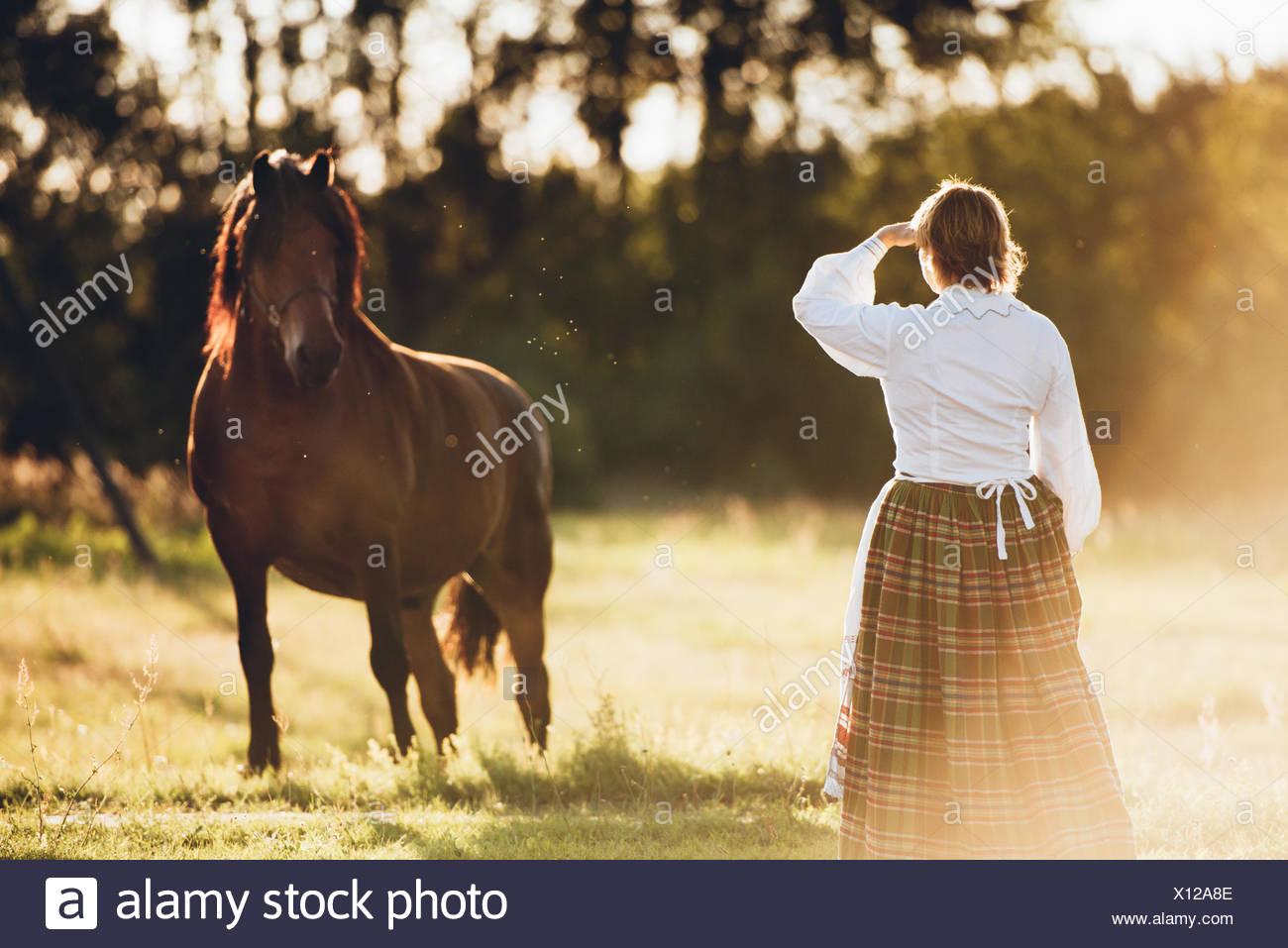 Vista posteriore della donna e cavallo in piedi sul campo Immagini Stock