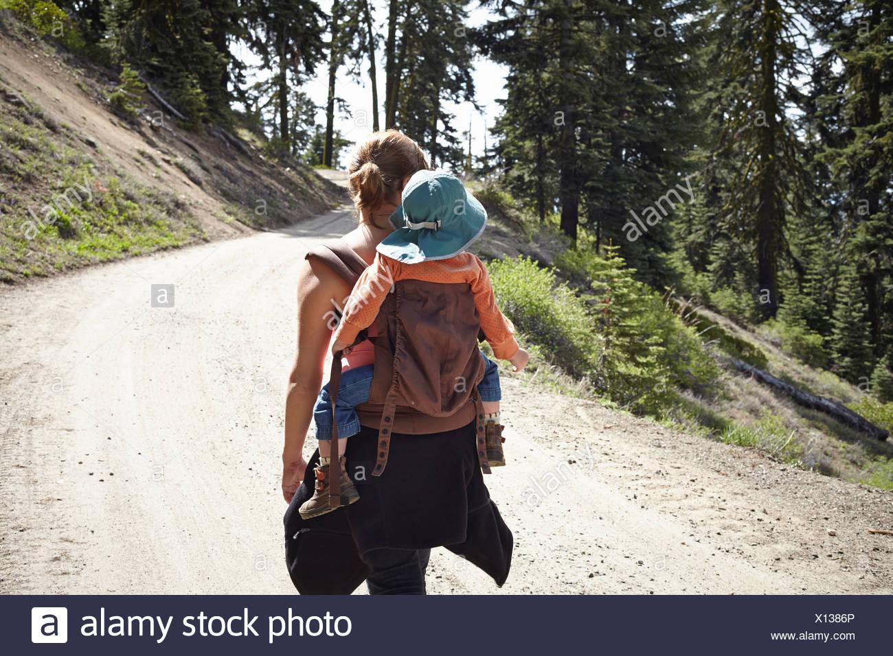 Vista posteriore della madre che trasportano il toddler in baby carrier Immagini Stock