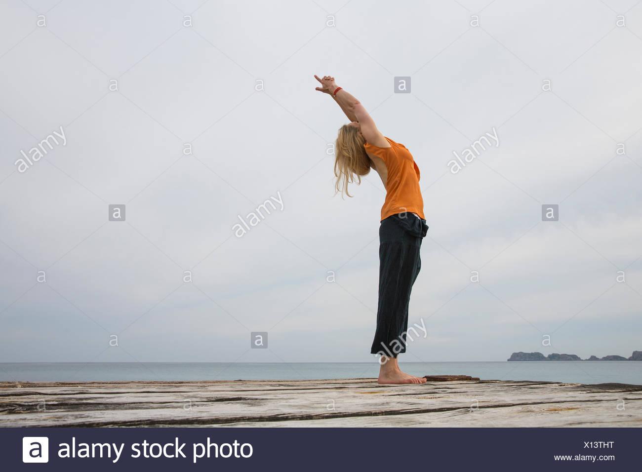 Metà donna adulta che risale a praticare yoga sul mare in legno pier Immagini Stock