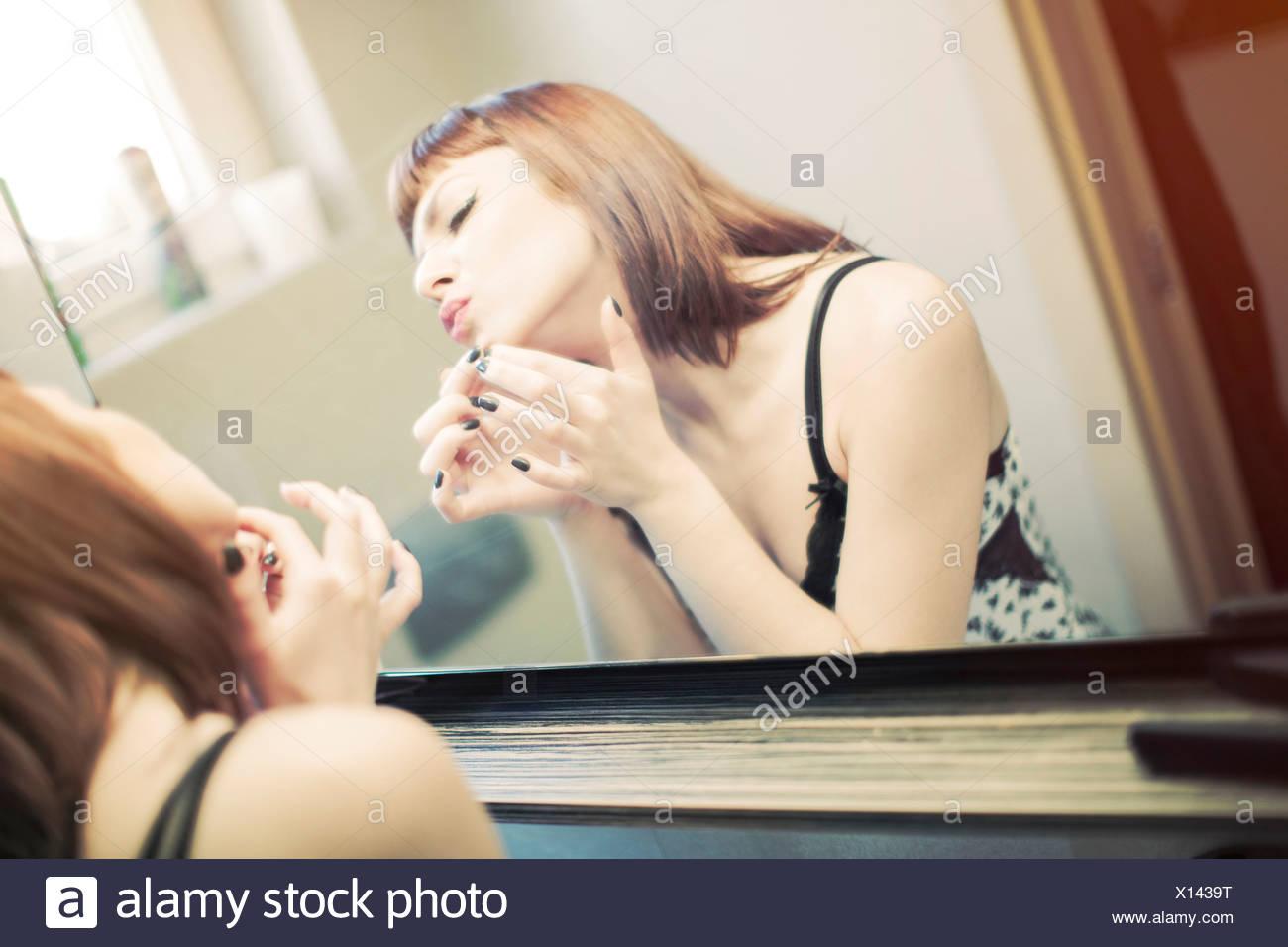 Giovane donna in nightie davanti a uno specchio Immagini Stock