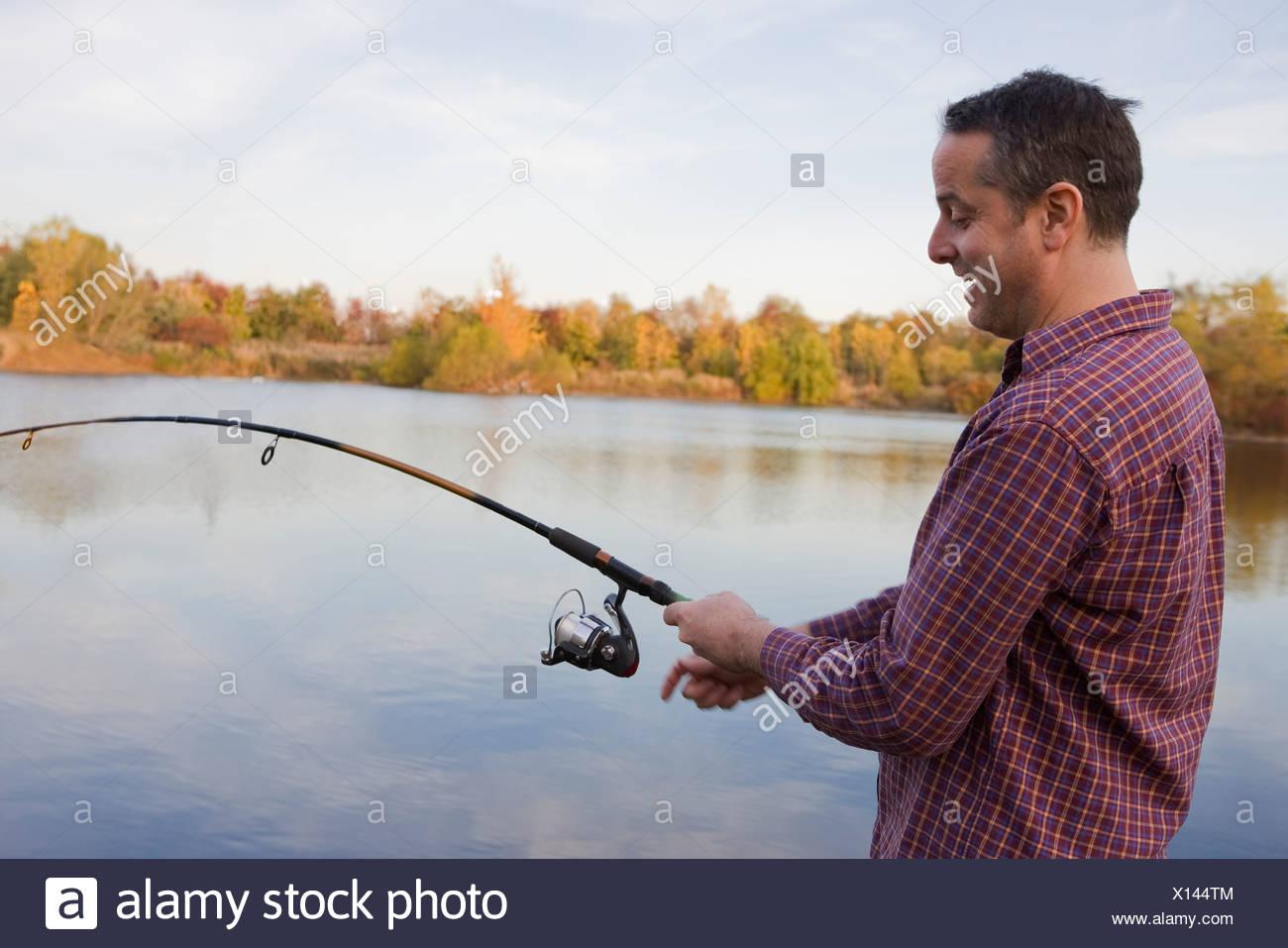 Maschio maturo pescatore la bobinatura in pesca dal lago Immagini Stock