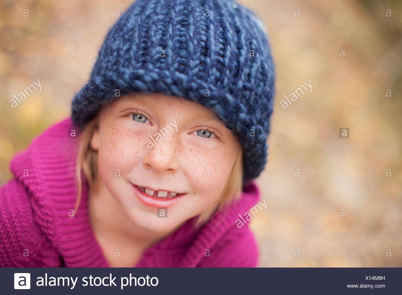 Una ragazza in un berretto lavorato a maglia e ponticello di magenta con un collare ripiegato. Immagini Stock