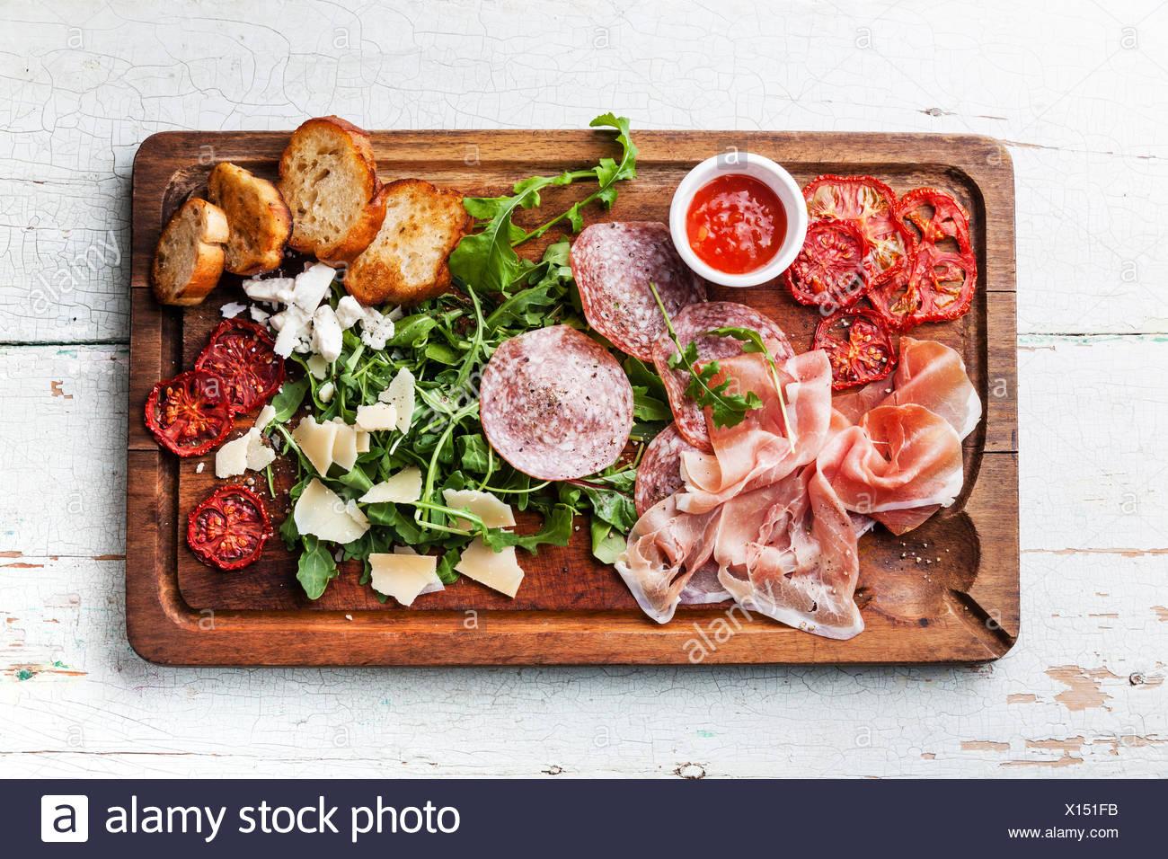Carne fredda piastra e il pane su sfondo di legno Immagini Stock