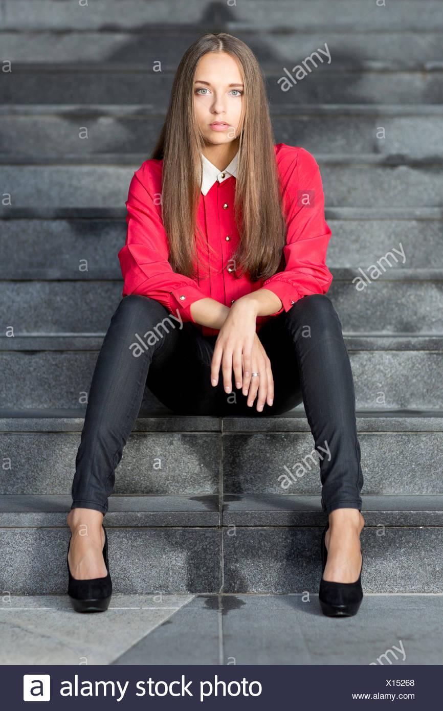 Giovane donna che indossa un top rosso, nero jeans e tacchi