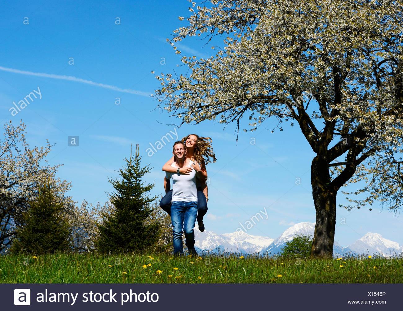 Uomo che porta una donna, sorridere di fronte a un albero di fioritura in primavera, Tirolo, Austria Immagini Stock