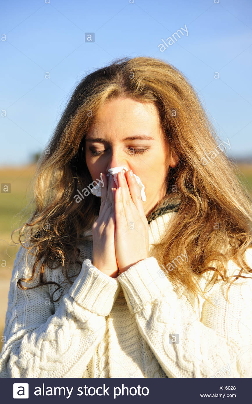 Donna soffia il naso all'aperto Immagini Stock