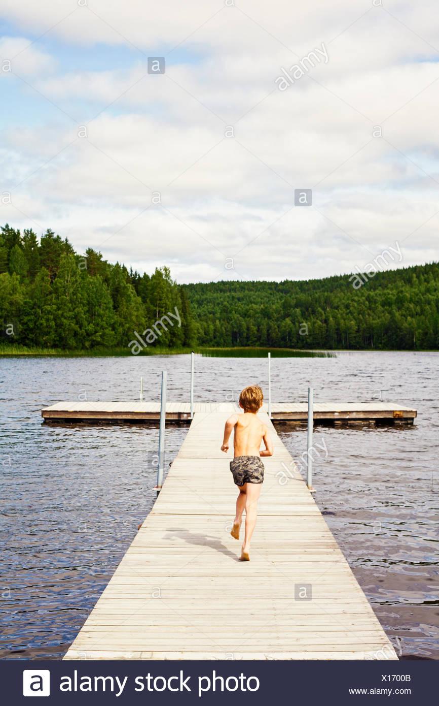 La Svezia, Uppland, Runmaro, Barrskar, vista posteriore del ragazzo (6-7) in esecuzione su jetty Immagini Stock
