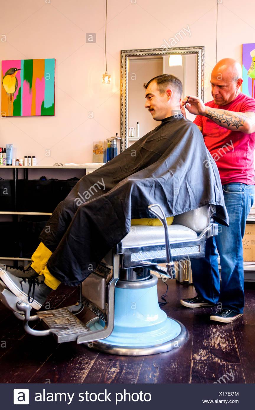 Giovane uomo avente il suo taglio di capelli Immagini Stock