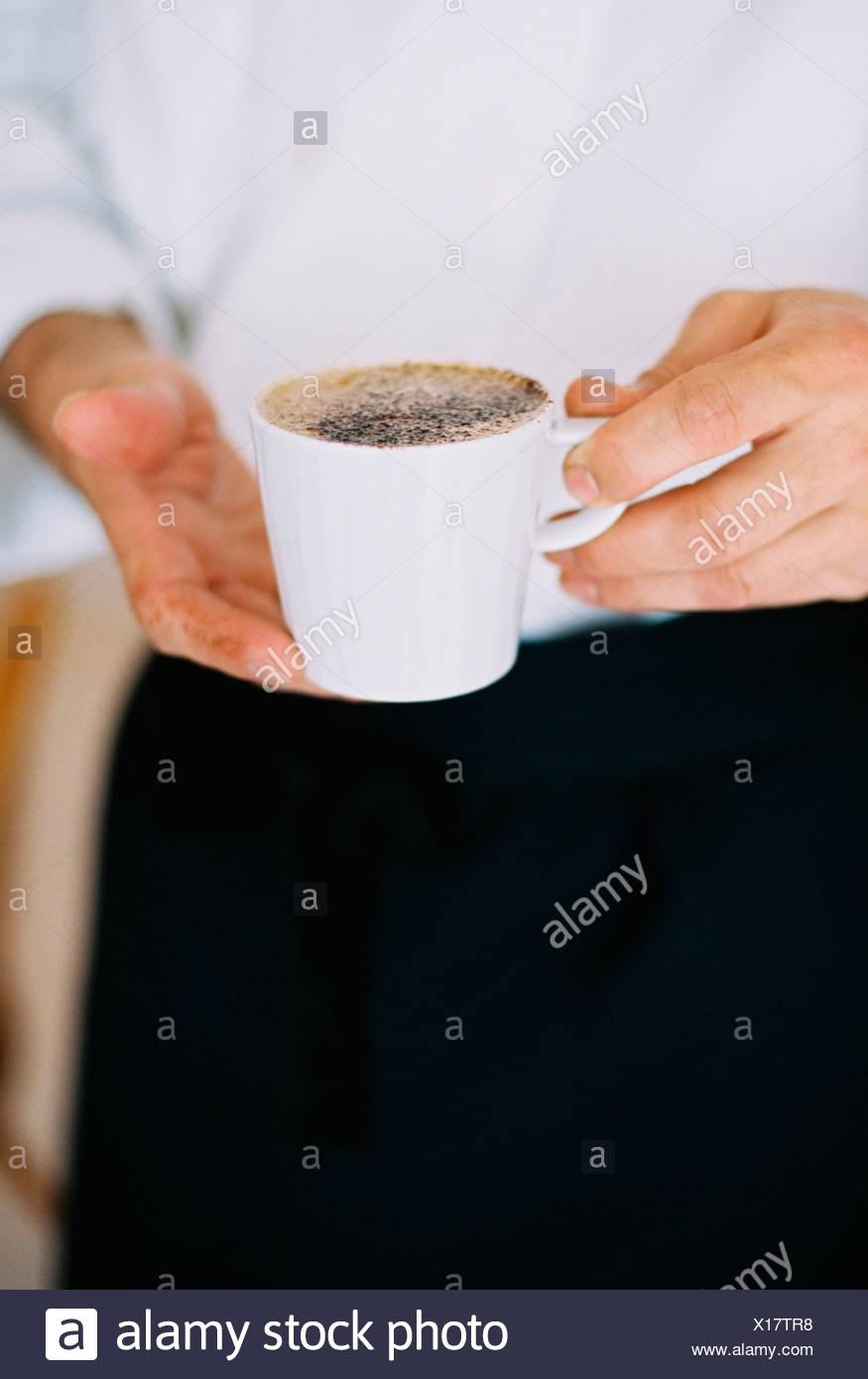 Una persona in possesso di una tazza piena di caffè. La schiuma. Immagini Stock