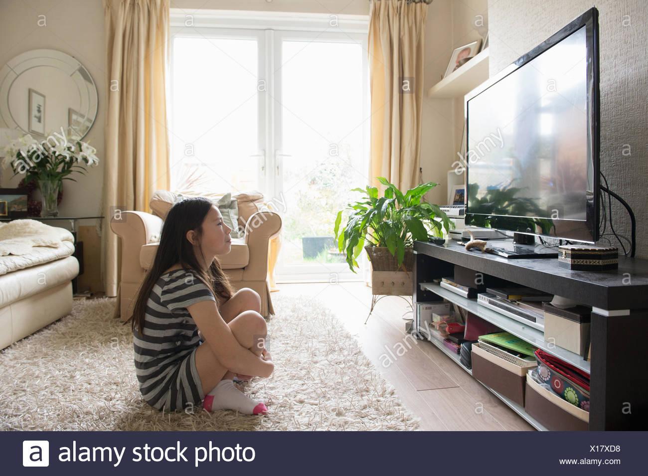 Ragazza seduta sul tappeto a guardare la televisione Immagini Stock