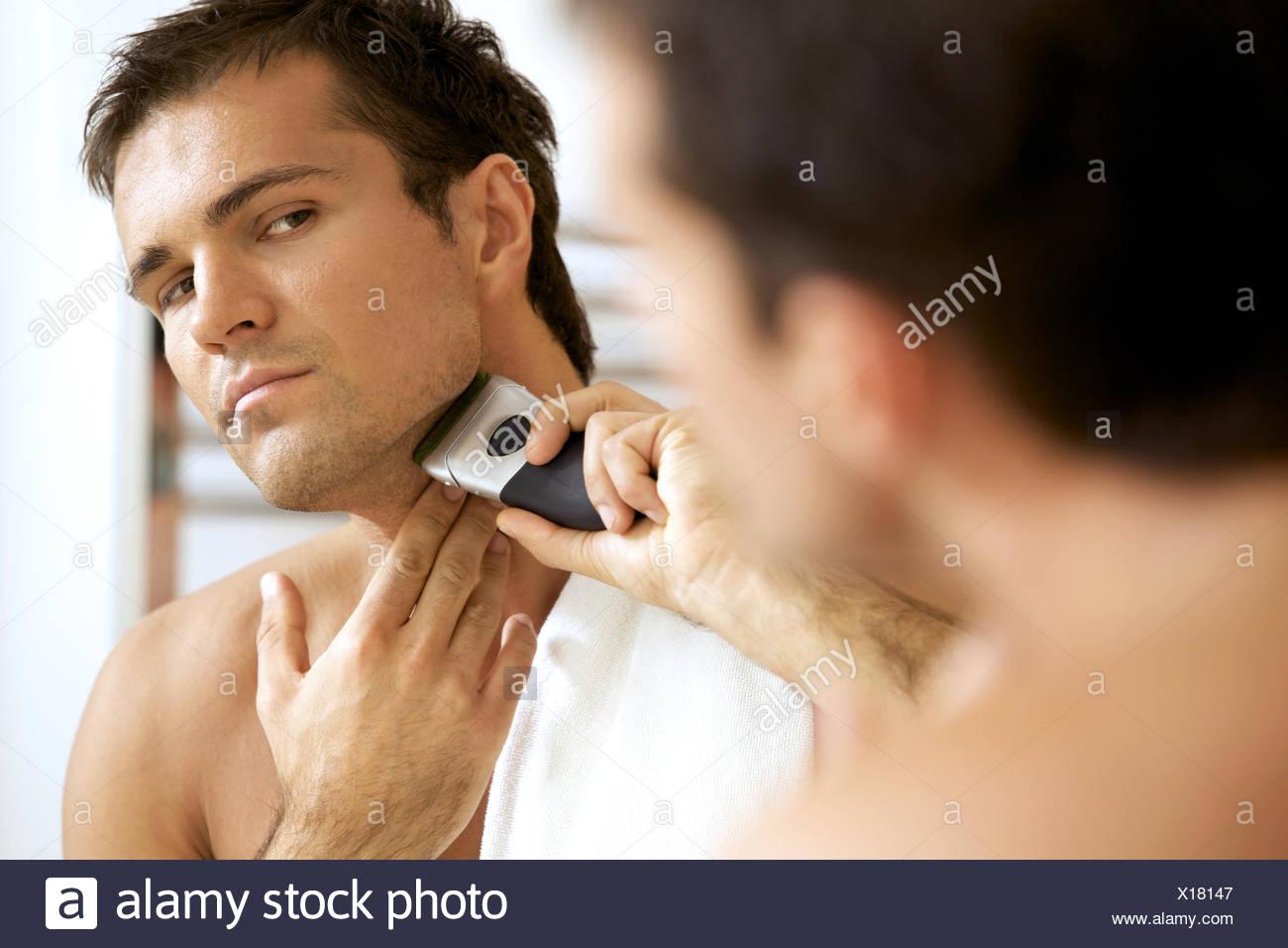 La riflessione del giovane uomo in mirror la rasatura con il rasoio elettrico Immagini Stock