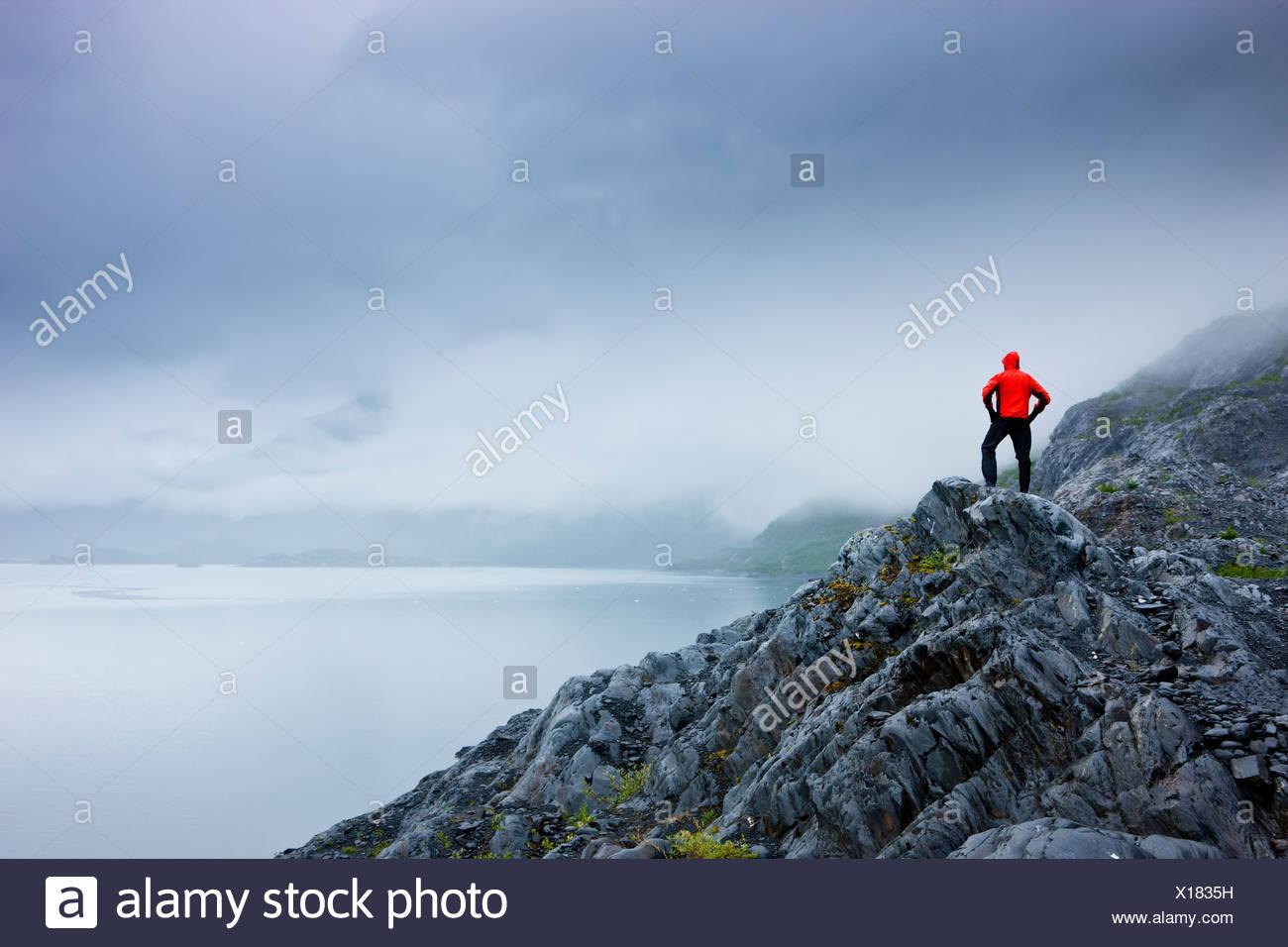 Un escursionista solitario sorge su un affioramento roccioso affacciato sulla Baia di Shoup membro Marine Park, Prince William Sound, Alaska Immagini Stock