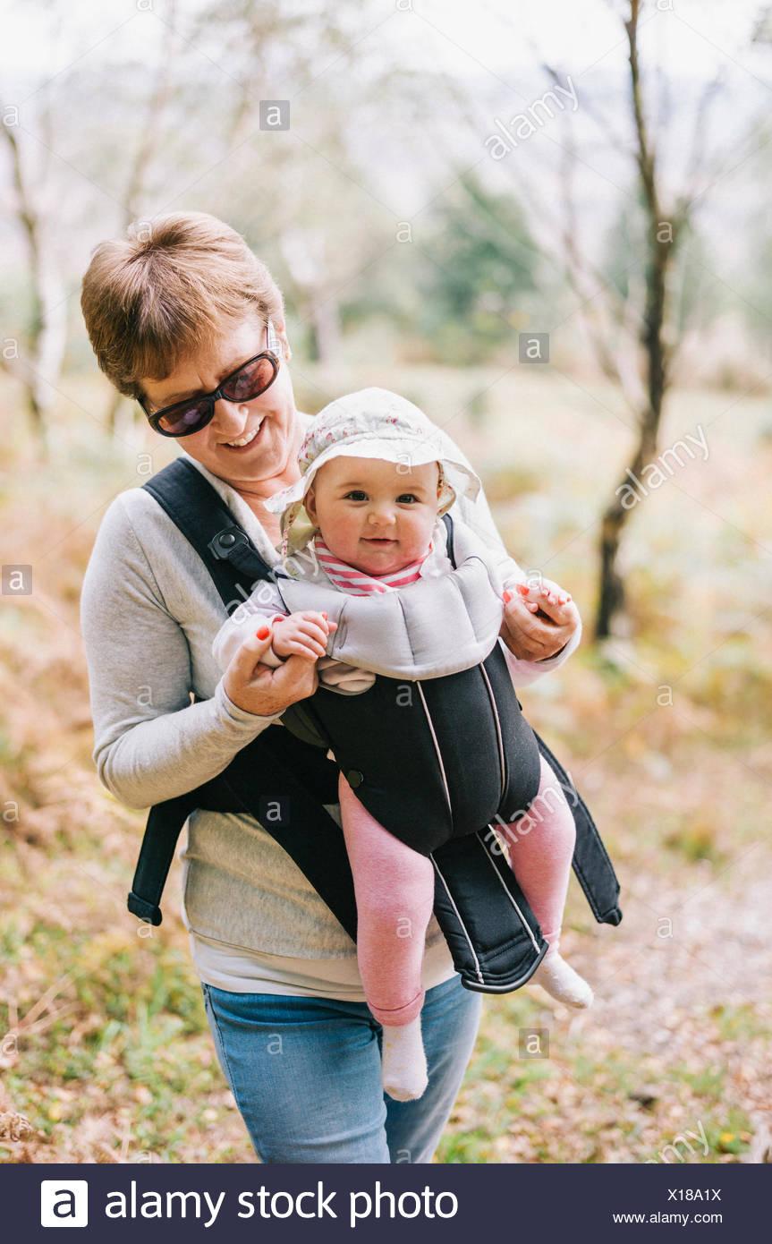 Una donna che indossa gli occhiali da sole che porta un bambino che indossa  un cappello bianco di fronte Baby Sling. 6103d94c825d