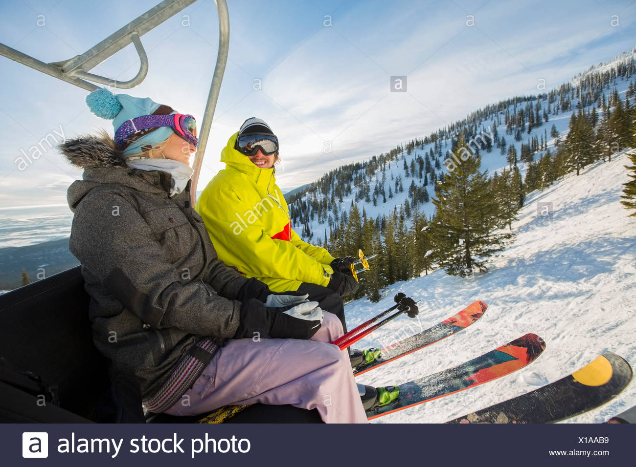 Matura in skiwear seduto su sci lift Immagini Stock