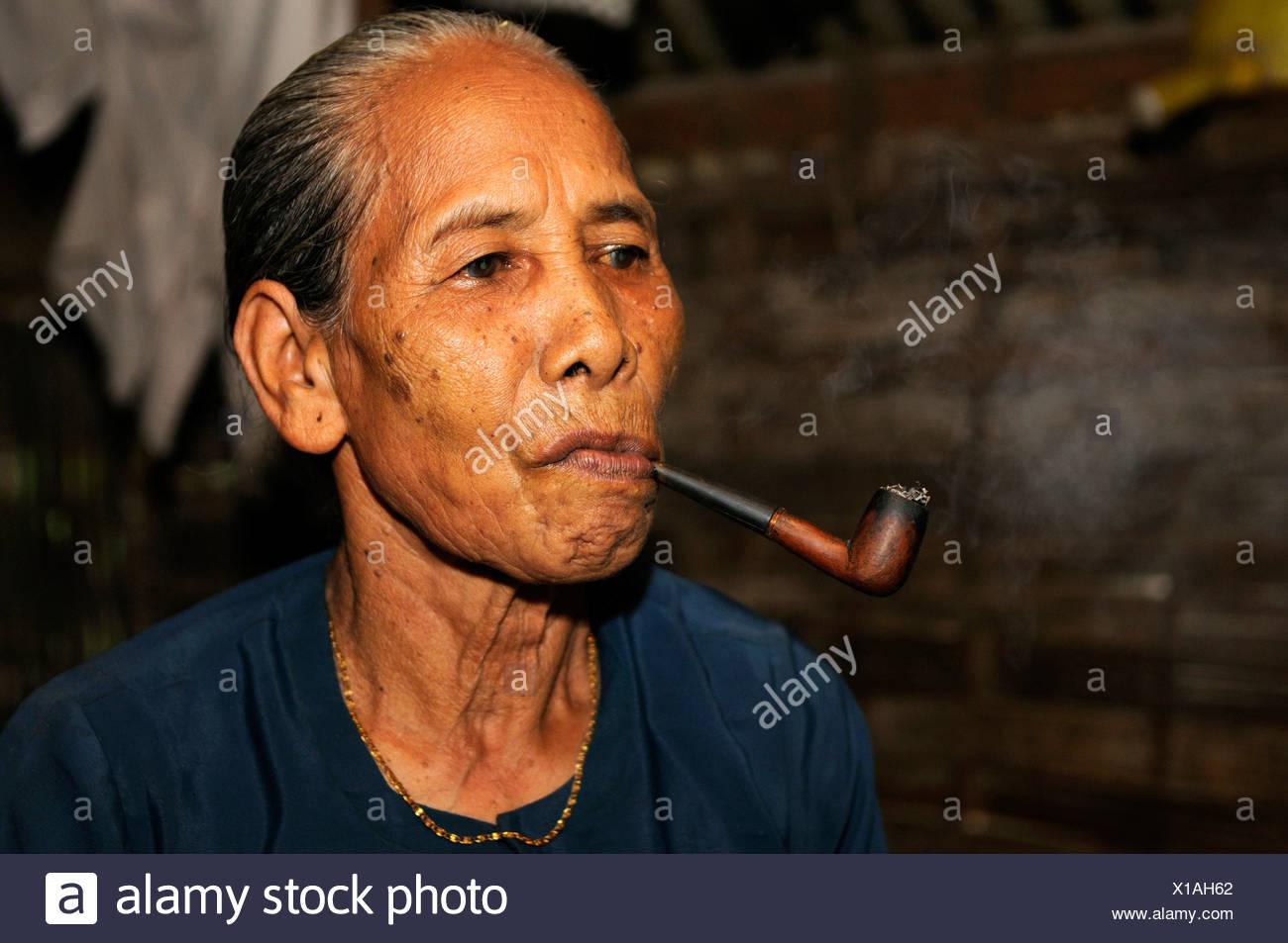 Vecchia donna fumare una tubazione, Vietnam, Asia Immagini Stock
