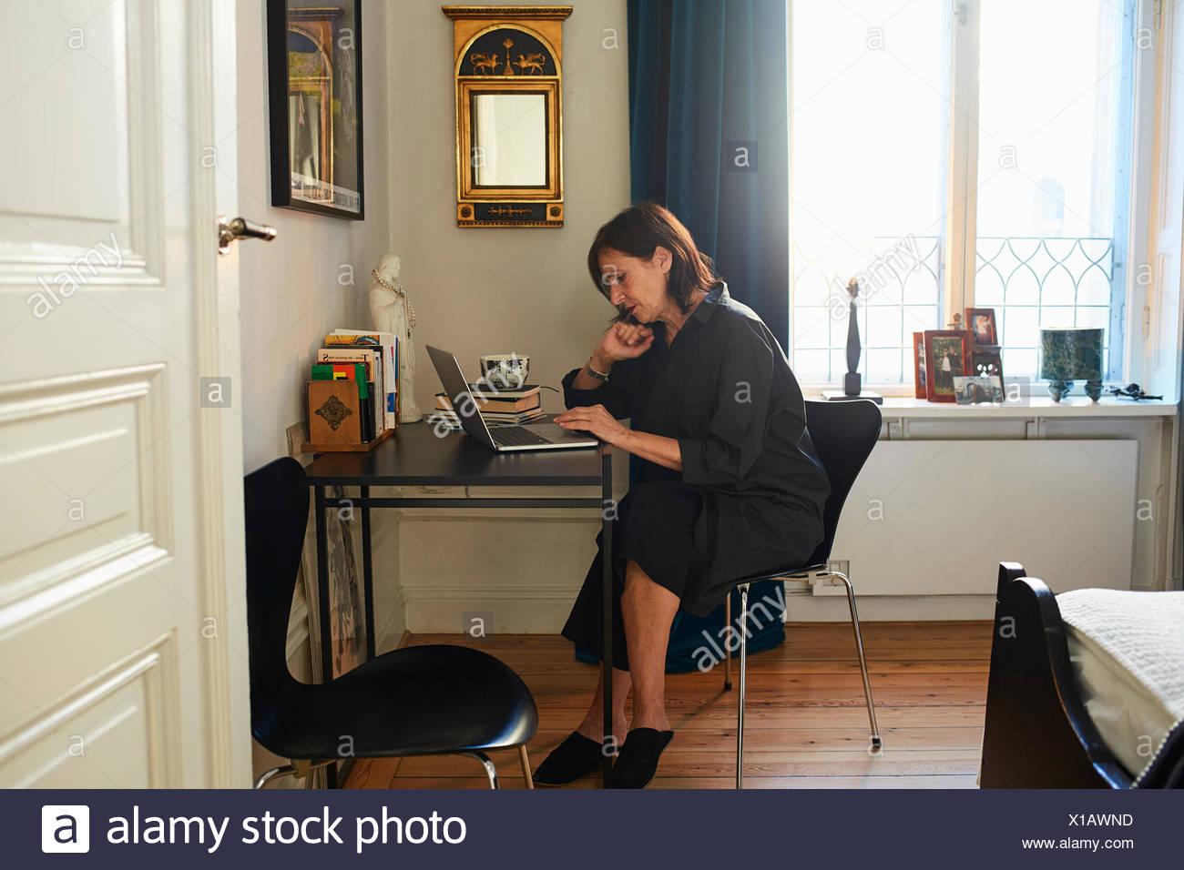 La Svezia, donna in abito nero utilizzando portatile a casa Immagini Stock
