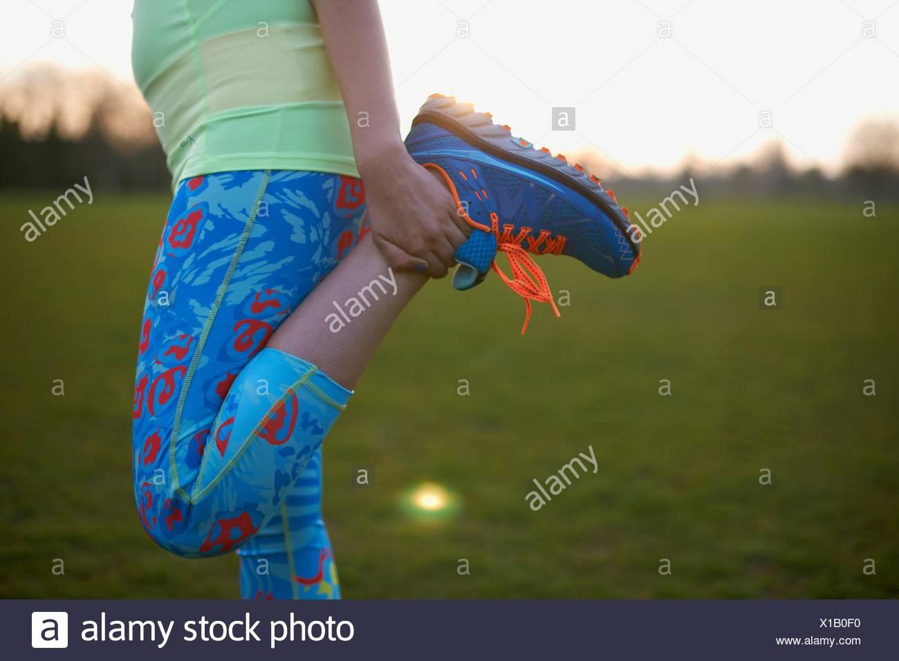Immagine ritagliata della donna lo stiramento della gamba per esercitare in posizione di parcheggio Immagini Stock