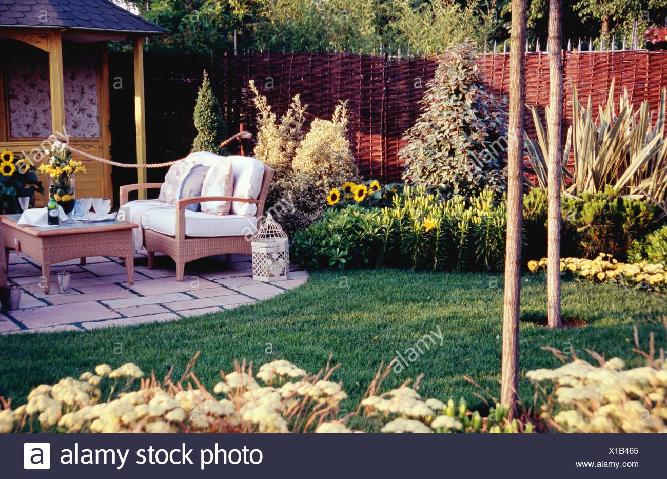 Piccolo giardino ben curato con aiuole di fiori pavimentato