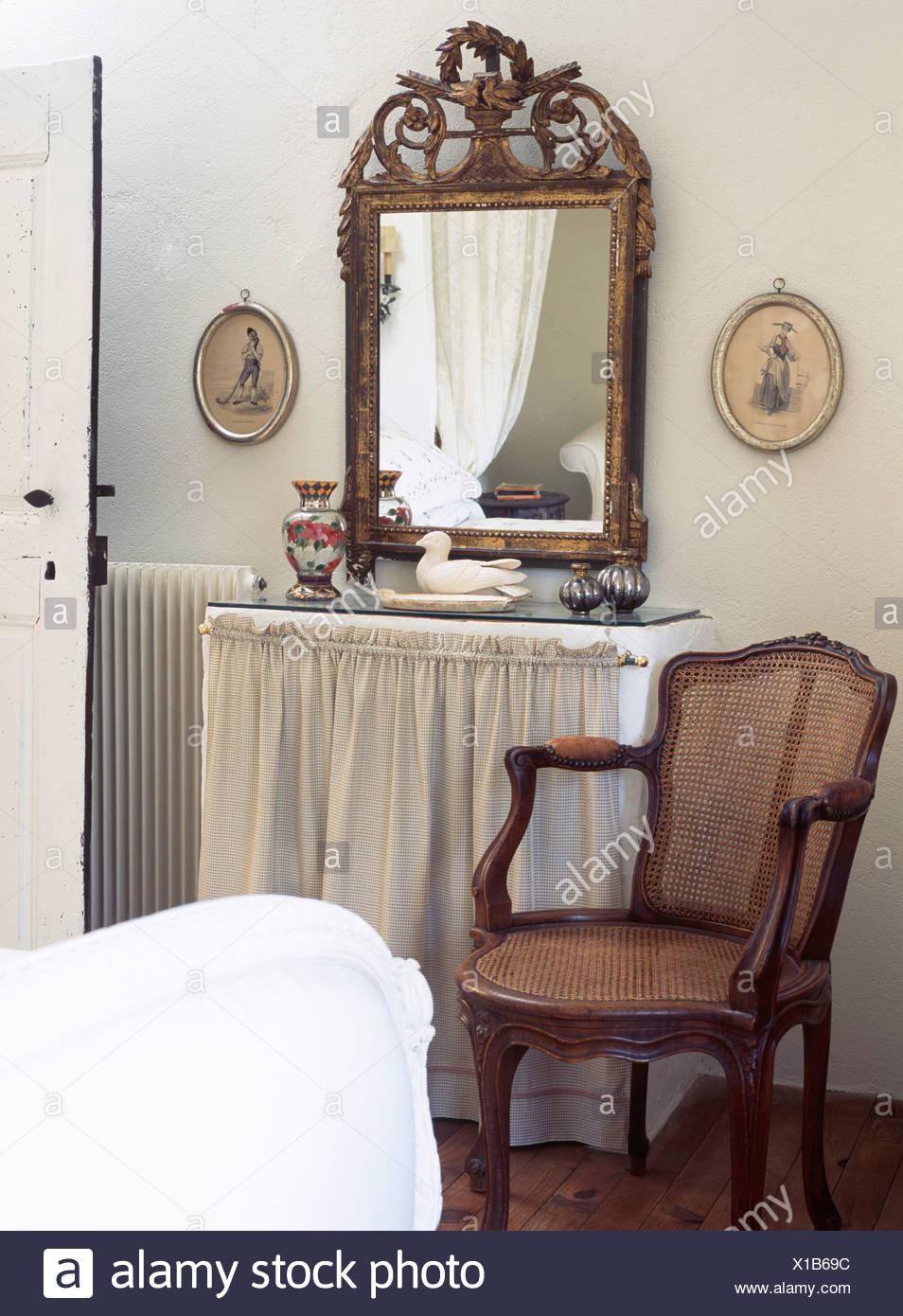 Antiquariato dorato ornata specchio sopra comò con drappi crema ...
