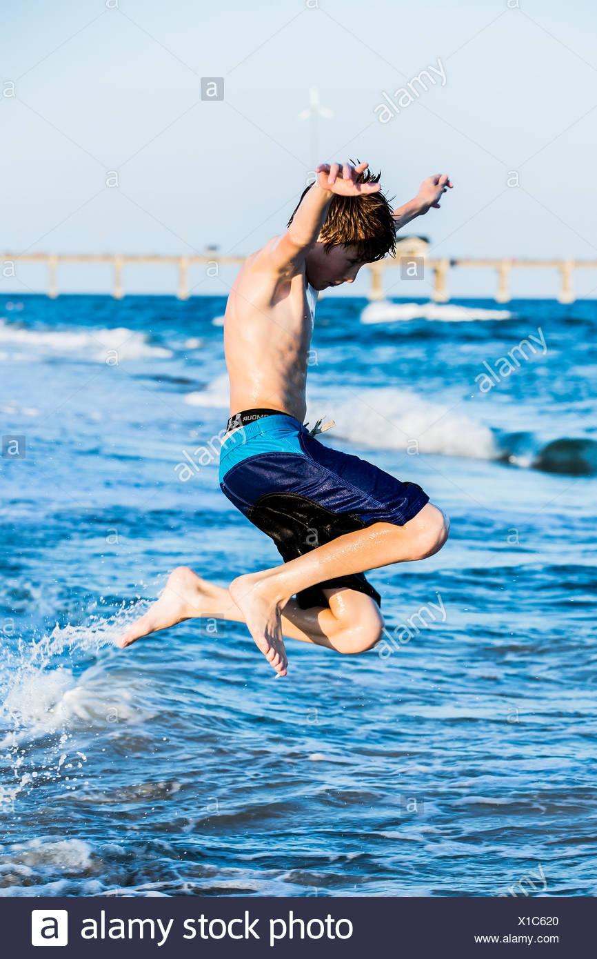 Redhead ragazzo sulla spiaggia il salto nel surf Immagini Stock