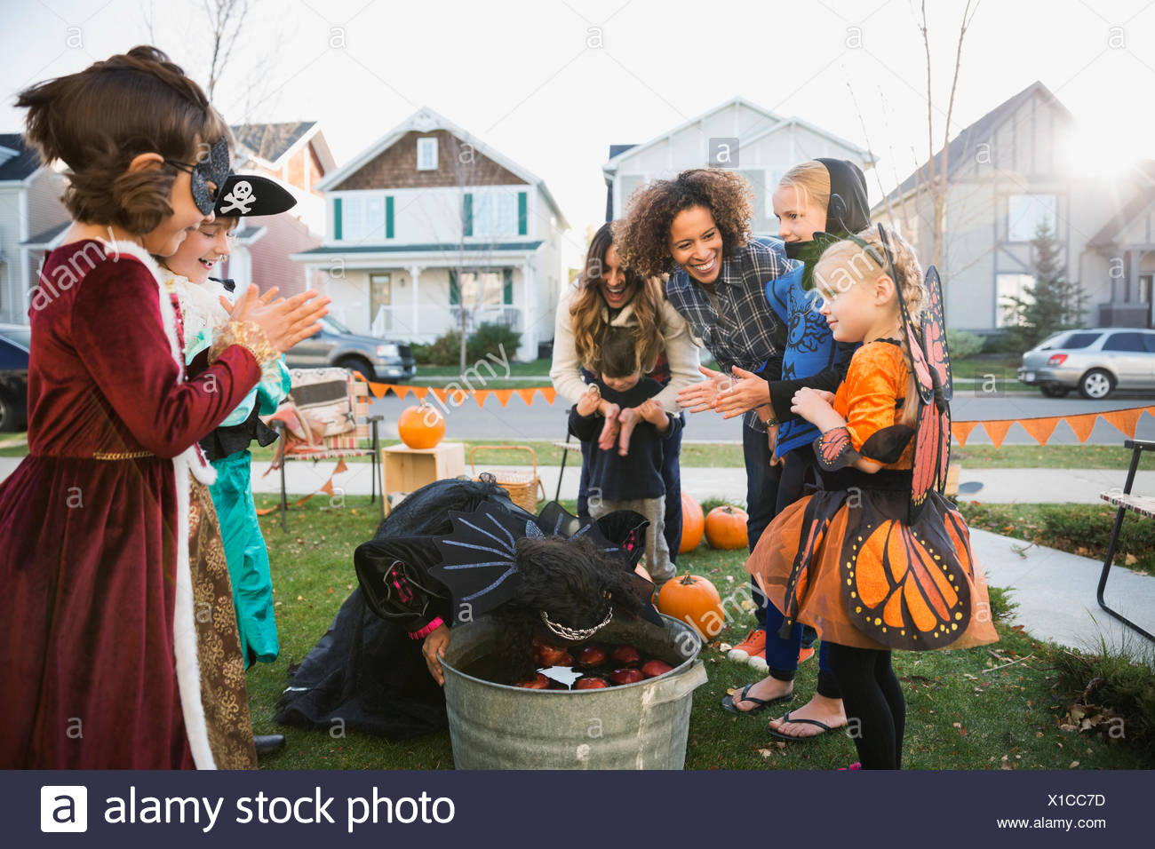 I bambini in costumi di Halloween bobbing per le mele Immagini Stock