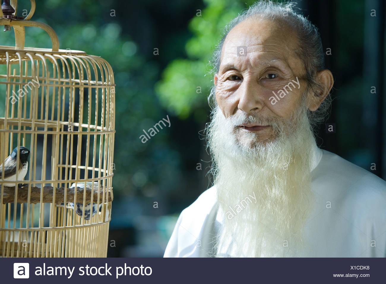 Uomo anziano che indossa il cinese tradizionale abbigliamento, con Bird Cage, ritratto Immagini Stock
